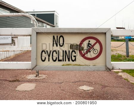 A Sign On Fence Saying No Cycling Dirty
