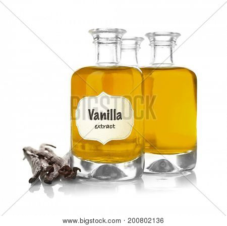 Bottles with aromatic extract and dry vanilla beans on white background