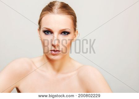 Attractive blonde topless woman with dark eye make up