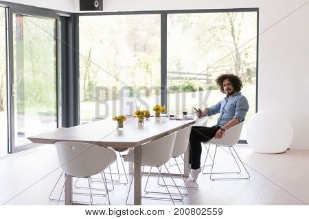 Handsome casual young man using a mobile phone at luxurious home