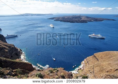 Summer holiday and vacation in Greece. Nature and environment. Traveling and wanderlust. Tourist ship and water transport. Panoramic view of old port and mediterranean sea in Santorini island.