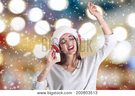 Young woman in Santa's hat with headphones listening to music and snow effect on blurred background. Christmas and New Year songs