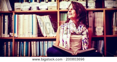Thoughtful female student sitting against bookshelf with book on library floor at college