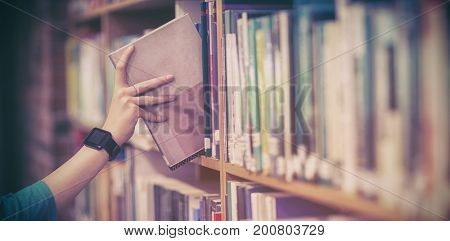 Students hand with smartwatch picking book from bookshelf at university