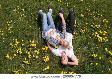 Overhead view of young man and woman lying on the grass, Top view of relaxed young couple lying down on meadow.