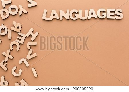 Word Language with pile of English letters on beige background, copy space. English language learning concept.