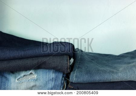 Blue jeans in a variety of  blue colors and condition on a shelf with copy space.
