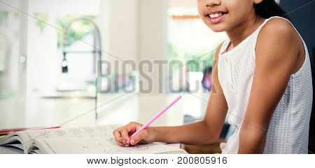Portrait of girl drawing in book at home