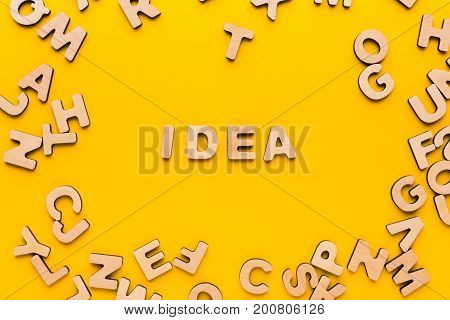 Word Idea on yellow background in wooden letters frame. Inspiration, creativity, imagination, brainstorm concept