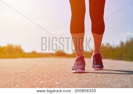 The girl runs along the road. Legs with sneakers.
