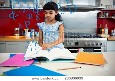 letters against girl flipping pages of book in kitchen
