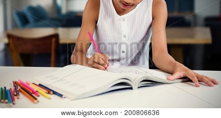 Concentrated girl drawing in book at home
