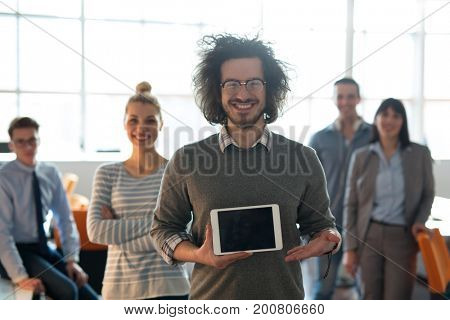 Portrait of a young businessman holding tablet in bright office with colleagues in the background