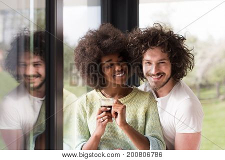 romantic happy young multiethnic couple enjoying morning coffee by the window in their luxury home