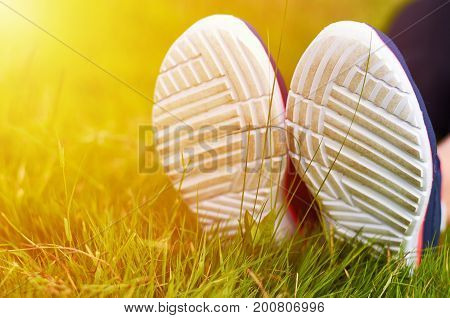 The legs of the girl in the sneakers lie on the green grass. Rest after sports. Concept of a healthy lifestyle and sport.