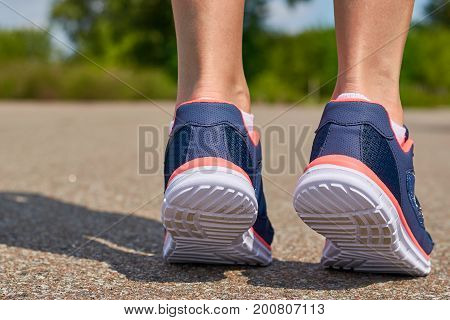 The girl is running in sneakers on the road. Concept of sport and healthy lifestyle.