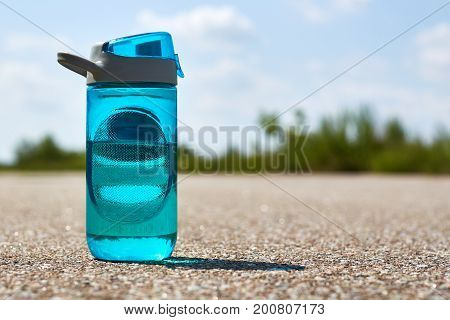 A sports bottle with water stands on the road. Concept of sport and refreshment.