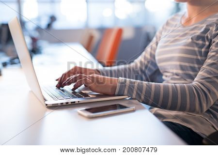 Young female Entrepreneur Freelancer Working Using A Laptop In Coworking space