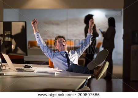 Full length of a relaxed casual young businessman sitting with legs on desk at night office