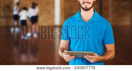 Portrait of sports teacher using digital tablet in basketball court at school gym