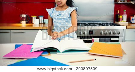 Girl flipping pages of book in kitchen at home
