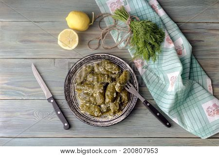 Dolmas in egg-lemon sauce in a plate on a wooden table close-up (Greek cuisine)