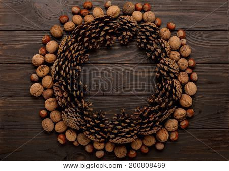 Flat lay frame cones and nuts on a wooden background. Selective focus.
