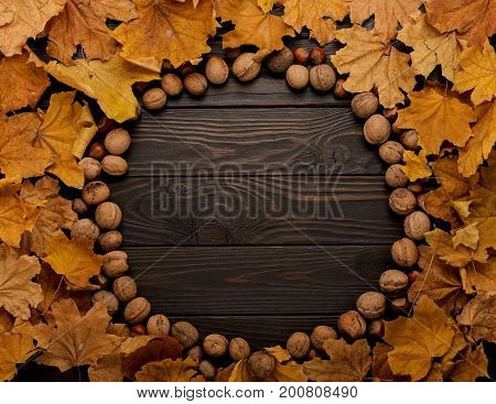 Flat lay frame of autumn leaves and nuts on a wooden background. Selective focus.