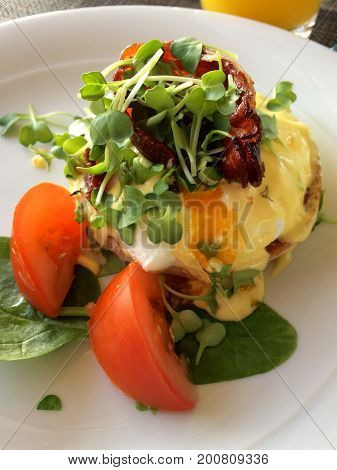 MAINZ, GERMANY - JUL 8th, 2017: Close up of Eggs Benedict with tomatos, spinach and bacon on a white plate with fresh herbs served in a luxury hotel.