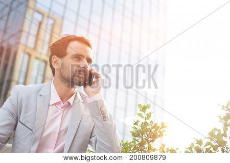 Businessman answering mobile phone outside office building