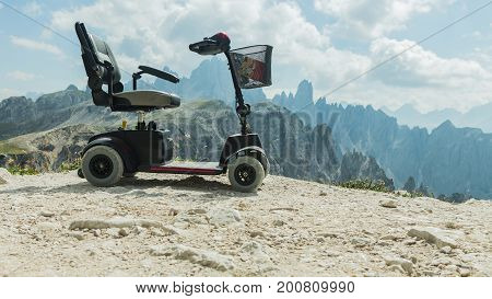 Mobile electric buggies on the mountain Dolomites Italy. Motorised wheelchair for disposable people disable car