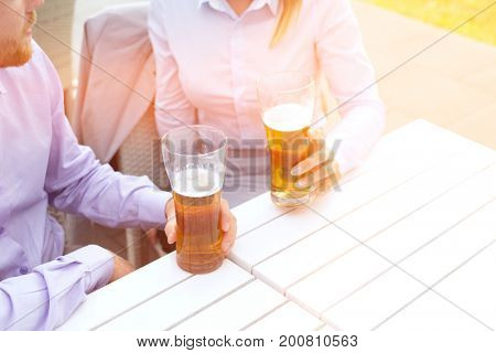 Midsection of business couple holding beer glasses at outdoor restaurant