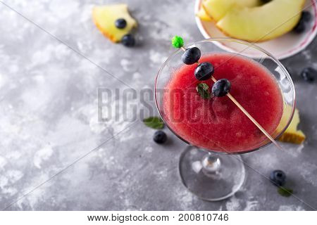 mellon ball cocktail served in a martini glass isolated on a stone background, copy space