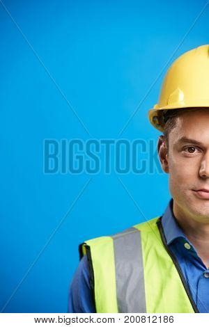 Young white construction worker in hard hat, vertical, crop