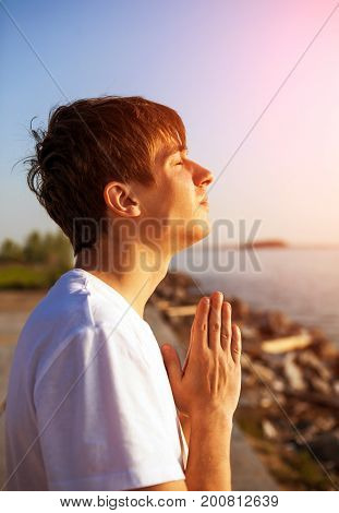 Young Man praying on the Nature Background