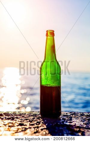 Bottle with a Dark Beer on the Sea Background