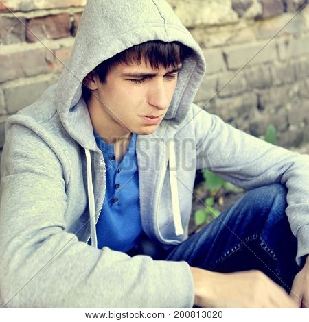 Toned Photo of Sad Teenager sit by the Brick Wall