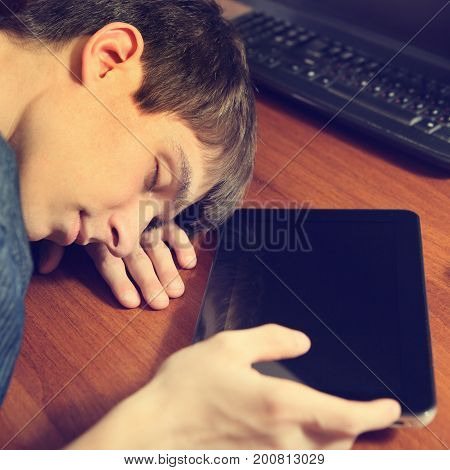 Toned Photo of Tired Teenager sleep with Tablet Computer on the Table