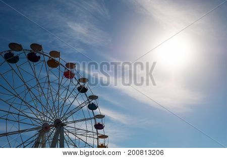 Ferris wheel on blue sky background and sun. In the amusement Park. The weekend