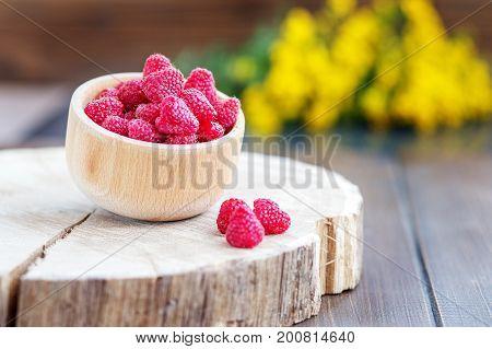 Fresh juicy raspberries in a wooden bowl. The concept is healthy food diet vegetarianism vitamins.