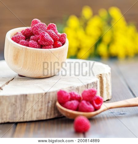 Juicy raspberries in a wooden bowl. Place for text. The concept is healthy food diet vegetarianism vitamins.