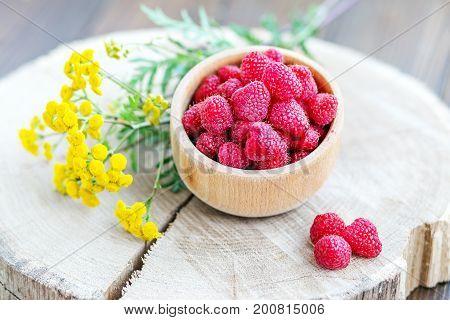 Tasty raspberries in a wooden bowl. Top view. The concept is healthy food diet vegetarianism vitamins.