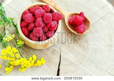 Tasty raspberries in a wooden bowl and a spoon. Top view. The concept is healthy food diet vegetarianism vitamins.