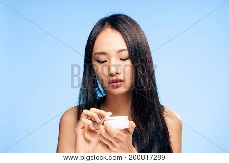 Beautiful young woman on a blue background holds a cosmetic face cream,Asian
