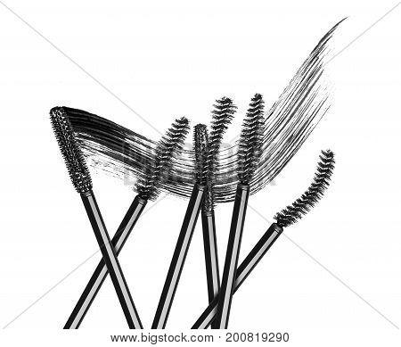 Various mascara brushes with mascara stroke on white background