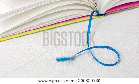 Book with blue bookmark on white table.