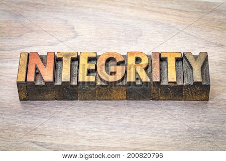 integrity - word abstract in letterpress wood type blocks against grained wood
