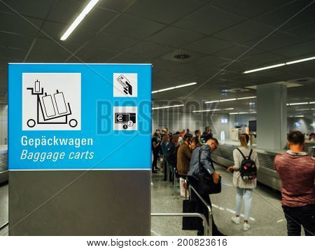 Unrecognizable passengers commuters waiting to claim the baggage luggage at modern airport next to illumination airport sign with baggage carts