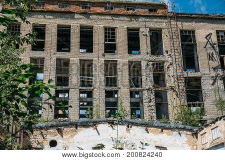 Facade of an abandoned factory building with broken windows