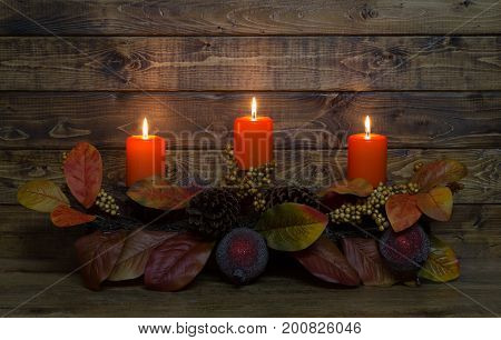 Burning autumn candles on a wood background